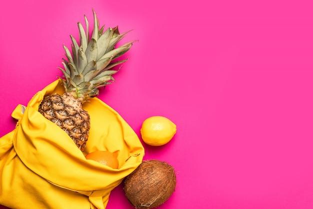 Tropische früchte mit einer gelben baumwolltasche auf einem rosa hintergrund.