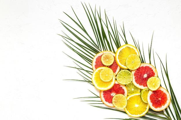 Tropische früchte und palmblätter auf einem weißen hintergrund, draufsicht.