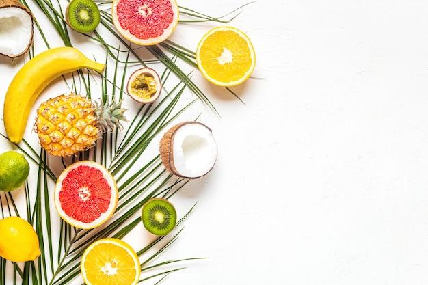 Tropische früchte und palmblätter auf einem weißen hintergrund