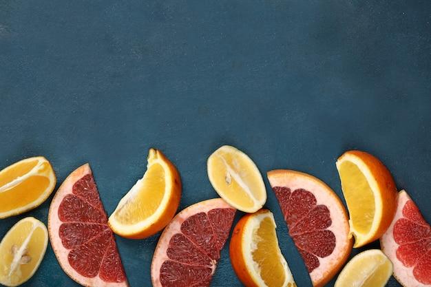 Tropische gestaltung mit geschnittener orange, zitrone und pampelmuse.