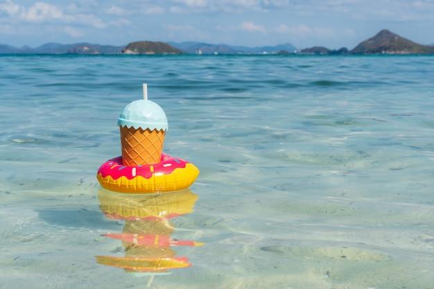 Tropische getränke, die auf tropisches meer mit kopienraum, sommerferien und reisekonzept schwimmen