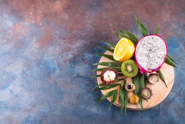 Tropische halbe fruchtzusammenstellung auf einem hölzernen runden spiel auf einem steinhintergrundmuster.