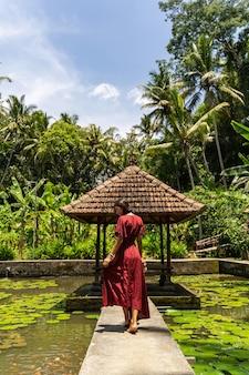 Tropische insel. begeisterte brünette frau, die auf steinstütze steht, während sie vor der kamera posiert, sonniger tag
