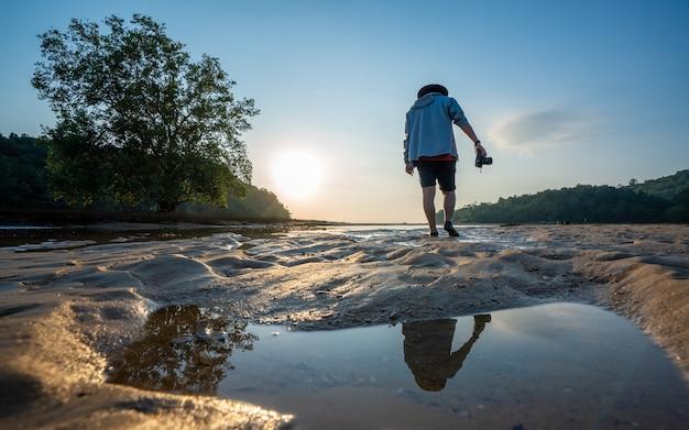 Tropische insel mit fotograf bei sonnenuntergang