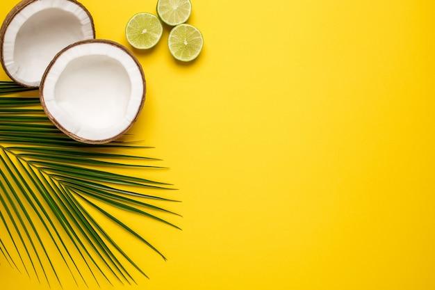 Tropische kokosnuss, palme und kalk auf einem gelb