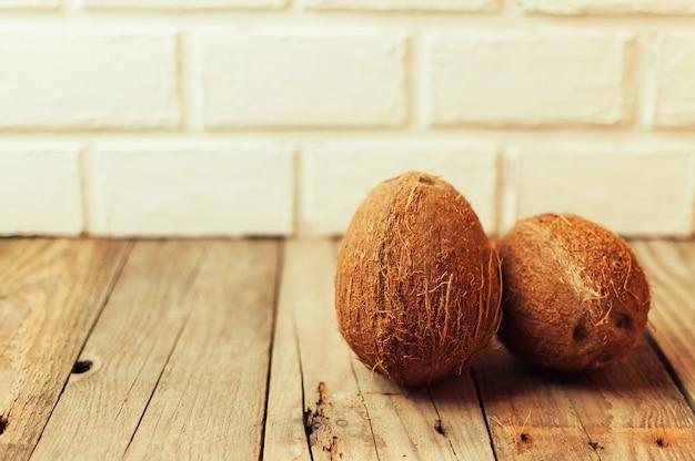 Tropische kokosnussfrüchte auf einem holztisch im rustikalen stil.