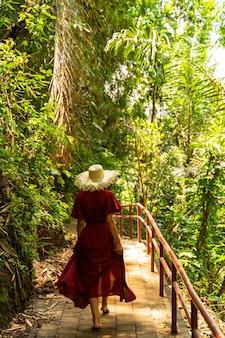 Tropische natur. entspannte weibliche person, die grüne pflanzen genießt, während sie ihren urlaub auf der insel verbringt