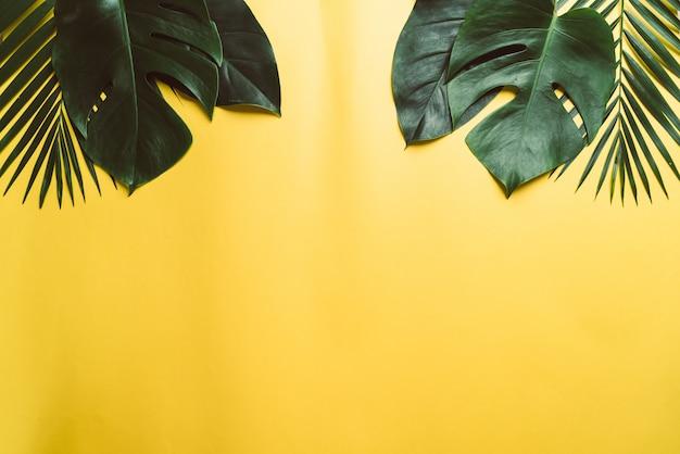 Tropische palmblätter auf gelbem hintergrund mit copyspace