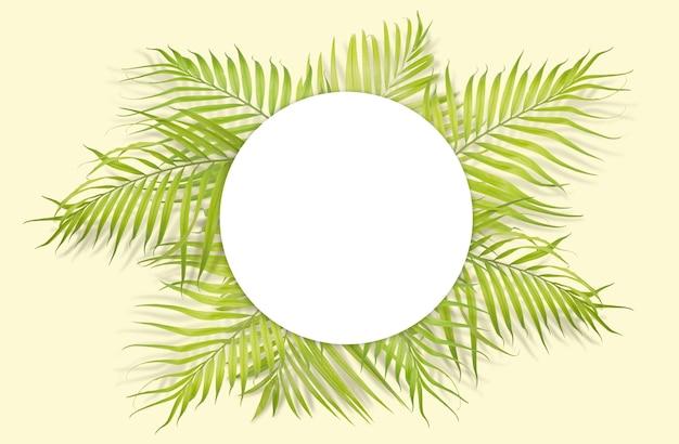 Tropische palmblätter mit weißem papier auf gelbem hintergrund.
