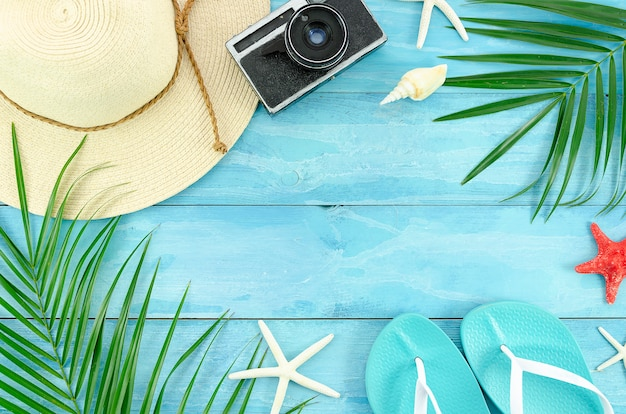 Tropische palmblattniederlassungen und -hut des sommers auf hölzernem plankenhintergrund