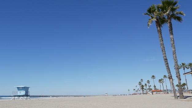 Tropische palmen am weißen sandstrand von meerwasserwellen, pazifikküste, oceanside kalifornien usa. blauer himmel und rettungsschwimmerturm. rettungsschwimmer-wachturmhütte, sommerufer. los angeles-vibes