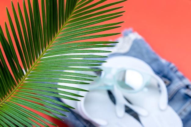 Tropische palmenzweige mit verschwommenen accessoires für die strandsaison