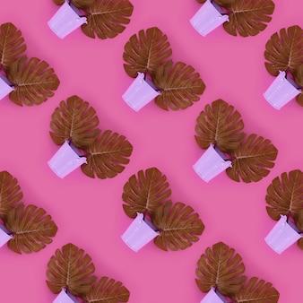 Tropische palmmonsterablätter liegen in den eimern eines pastells auf rosa