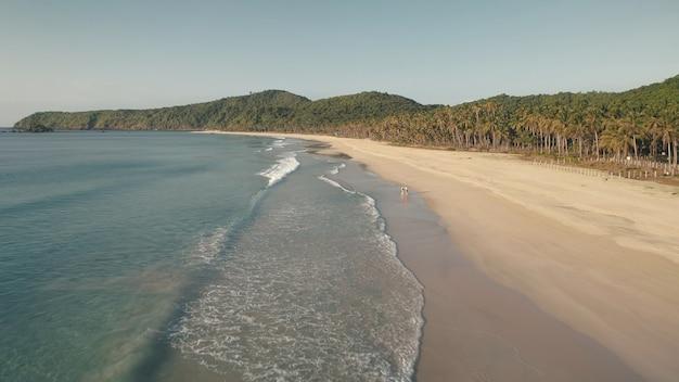 Tropische seelandschaft der ozeanbuchtantenne. touristen walzen am sandstrand. berg mit tropischen palmen