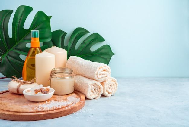 Tropische spa-zusammensetzung mit hautpflegeprodukten, monstera-blättern und orangenöl.