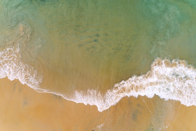 Tropische strand-meereswelle der luftansicht, die auf weißen meeresschaum des sandufers spritzt.