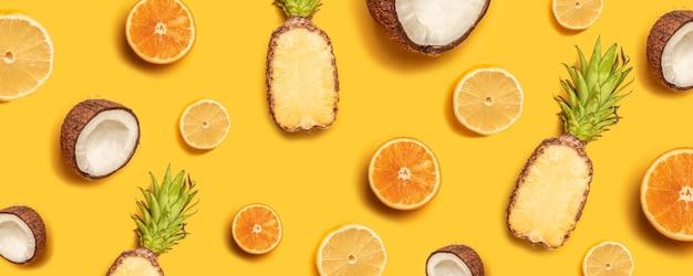 Tropischer abstrakter hintergrund. ananas, zitronen, orangen und kokosnüsse auf einem gelben hintergrund.