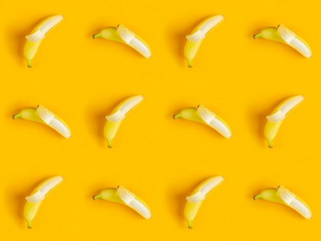 Tropischer abstrakter hintergrund. saftiges reifes bananenmuster auf gelbem hintergrund oben