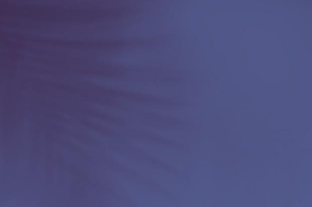 Tropischer blattschatten auf trendigem monochromem dunkelblauem hintergrund.