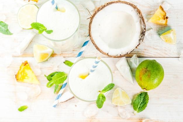 Tropischer cocktail, pina colada, ananas und kokos-mojito oder smoothies mit limette und minze auf hellblauem untergrund