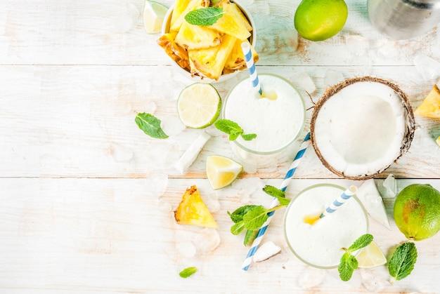 Tropischer cocktail pina colada ananas und kokosnuss mojito oder smoothies mit kalk und minze auf einem hellblauen hintergrund
