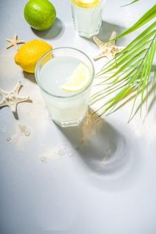 Tropischer hintergrund der sommerferienferien mit limonadengetränken. mojito-cocktail mit harten hellen und dunklen schatten, auf einem tropischen hintergrund mit seestern, palmblätter kopieren raum für text