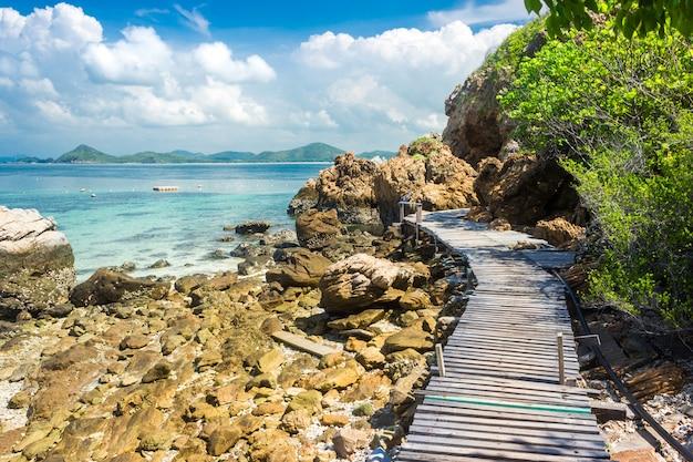 Tropischer inselfelsen und holzbrücke am strand mit blauem himmel.