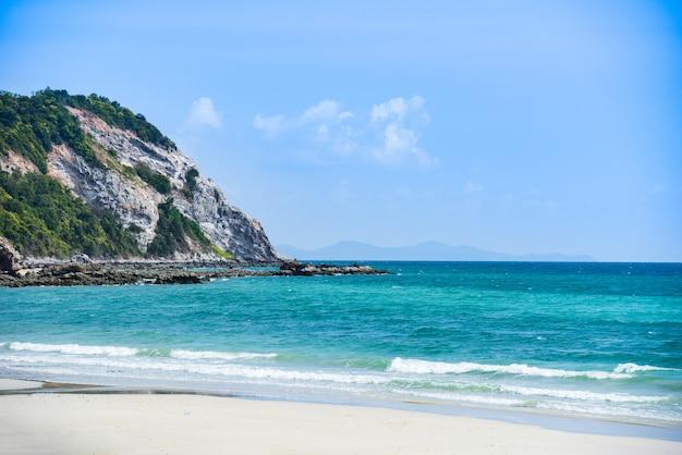 Tropischer meersommer des strandsandes / schönes strandklares wasser der insel und schwermütiger blauer himmel mit hügelfelsen