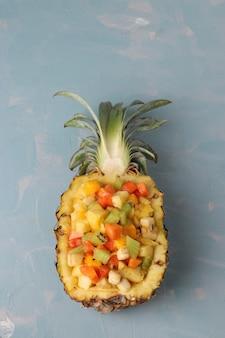Tropischer obstsalat in ananashälften auf hellblauem hintergrund, nahaufnahme, draufsicht, vertikale ausrichtung