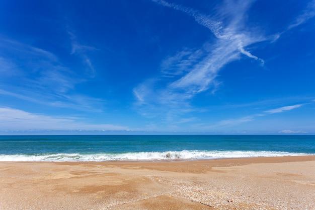 Tropischer sandiger strand mit hintergrund des blauen ozeans und des blauen himmels