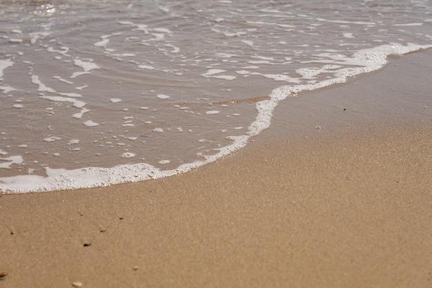 Tropischer sandstrand mit wellen und schaum.