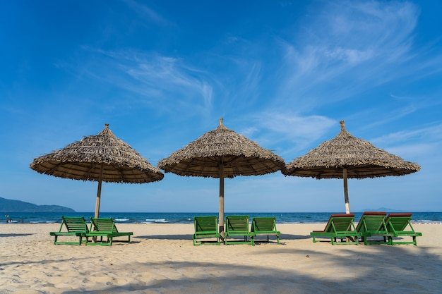 Tropischer sandstrand und sommerliches meerwasser mit blauem himmel und drei strohschirm in danang stadt