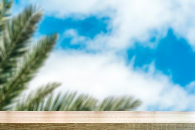 Tropischer schreibtischtischhintergrund verwischte tropischen palmzweig gegen den hintergrund