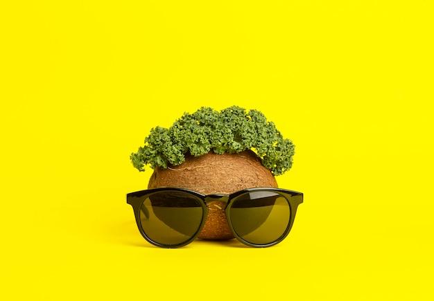 Tropischer sommerhintergrund. sonnenbrille, kokosnuss und grünblätter auf einem gelben hintergrund. lustiges gesicht aus früchten. minimales kreatives konzept
