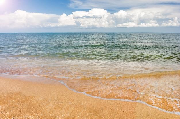 Tropischer strand des marinesandes und blauer himmel mit wolken