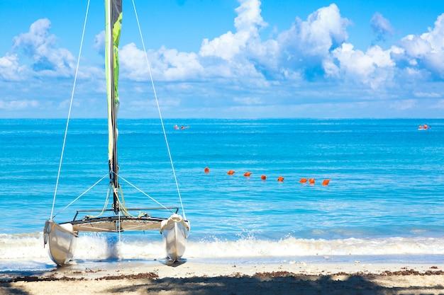 Tropischer strand mit einem bunten segelboot an einem sommertag mit türkisfarbenem wasser und blauem himmel. varadero resort, kuba.
