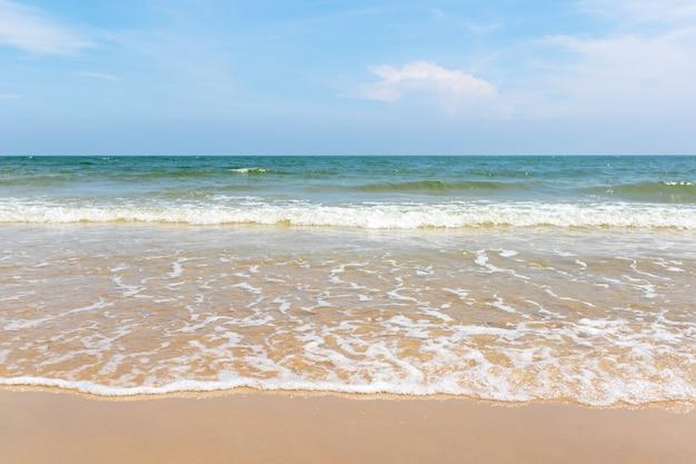 Tropischer strand mit grünem ozean und kleiner welle.
