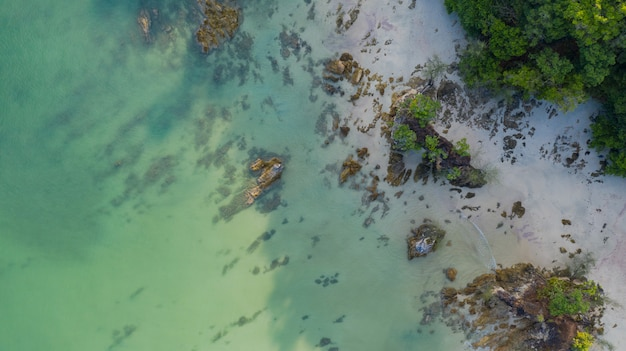 Tropischer strand mit ozean und felsen auf der insel