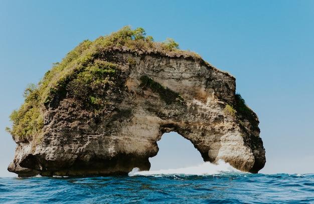 Tropischer strand mit perforierten klippen in canggu bali