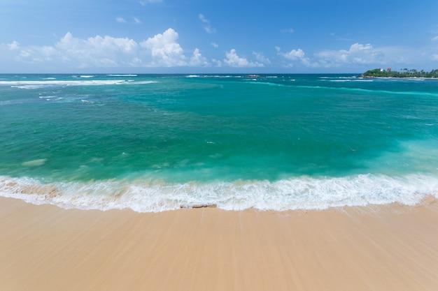Tropischer strand und wellenartig bewegender ozean des blauen grüns