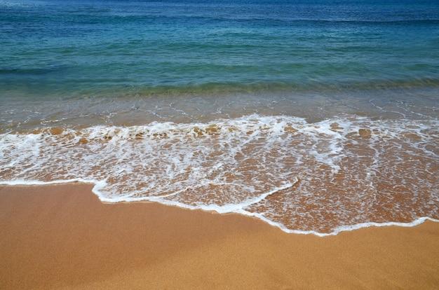 Tropischer strandhintergrund mit blauem ozeanwasser mit wellen und gelbem sand. abstrakte seelandschaft. sommerferienkonzept.