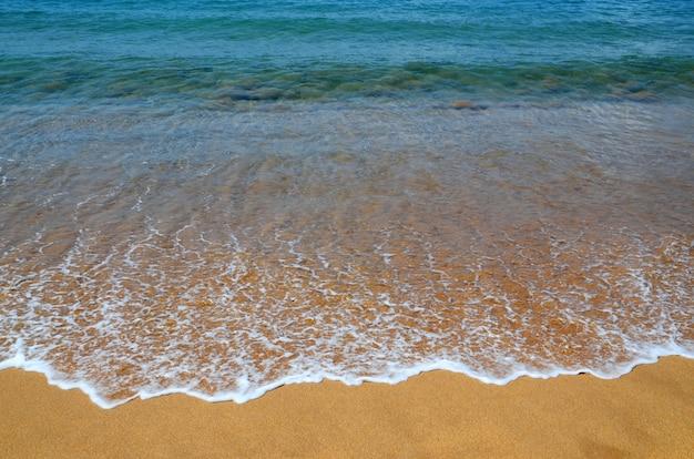 Tropischer strandhintergrund mit blauem ozeanwasser mit wellen und gelbem sand. abstrakte seelandschaft. sommerurlaub oder entspannungskonzept.