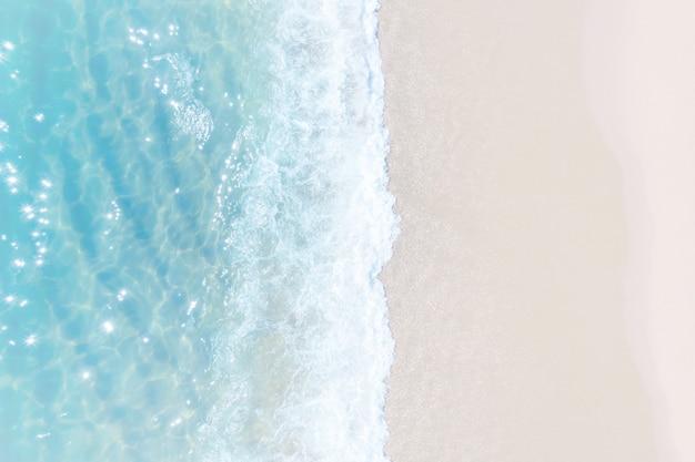 Tropischer strandwasserhintergrund. weiche welle des smaragdgrünen klaren meeres am sandstrand