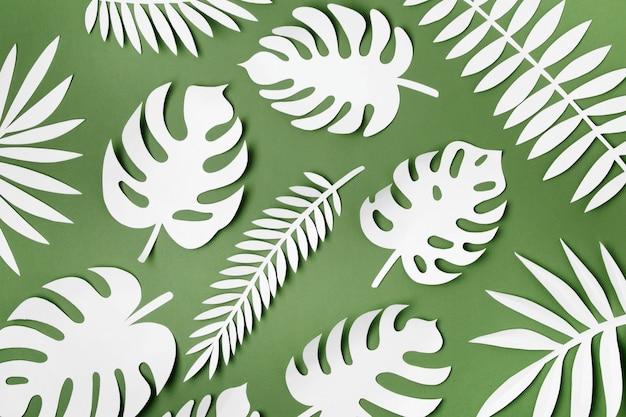 Tropisches blattmuster. verschiedene papierblätter auf grünem hintergrund. papierkunst. flache lage, ansicht von oben