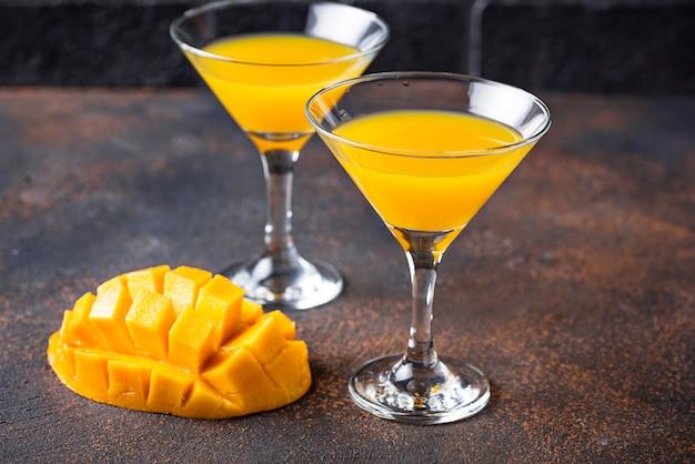 Tropisches cocktail mit mango auf dunklem hintergrund