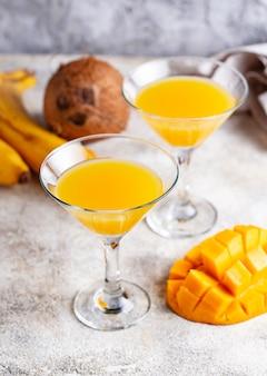Tropisches cocktail mit mango auf hellem hintergrund