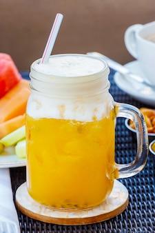 Tropisches cocktail, mocktail, saft, auffrischungsgetränk von der maracuja im glasgefäß auf tabelle im café.