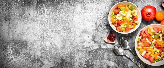 Tropisches essen frischer obstsalat auf rustikalem hintergrund
