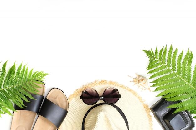 Tropisches ferienmuster. strohstrand sunhat, sonnenbrillen, strandklaps, blatt des farns auf weiß.