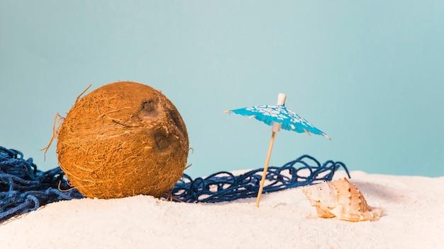 Tropisches konzept mit kokosnuss und strandschirm